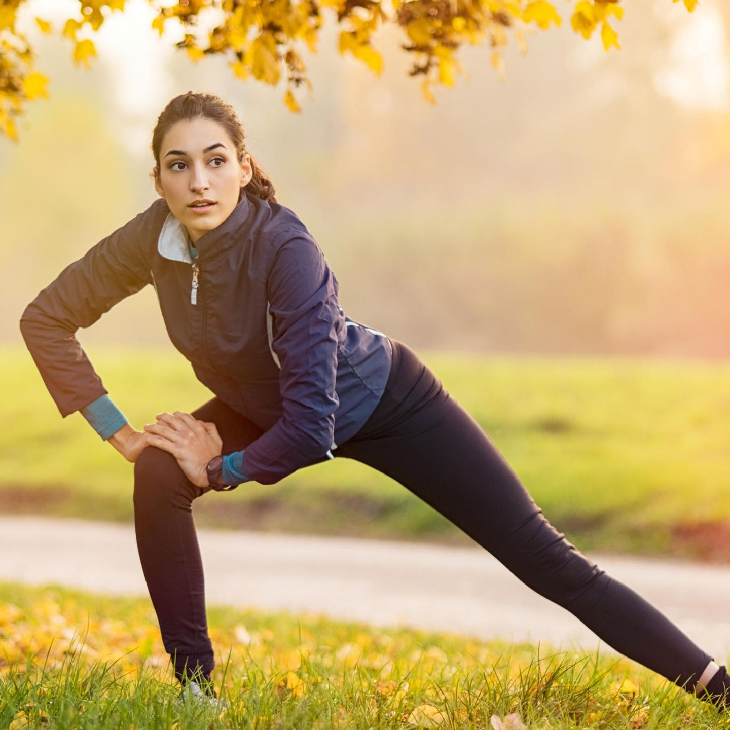 Healthy living: woman stretches in autumn park