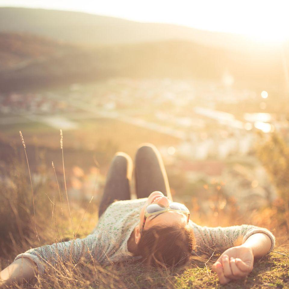 gesund leben: Frau entspannt auf einem Hügel