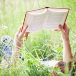Bücher für den Urlaub: Frau mit Buch auf der Wiese