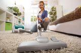 Sport nebenbei: Frau hat Spaß beim Wohnung putzen