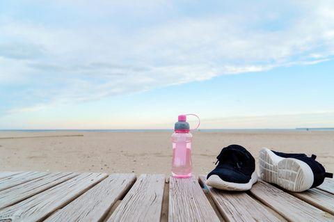 Trainingspause: Schuhe und Trinkflasche vor Strand