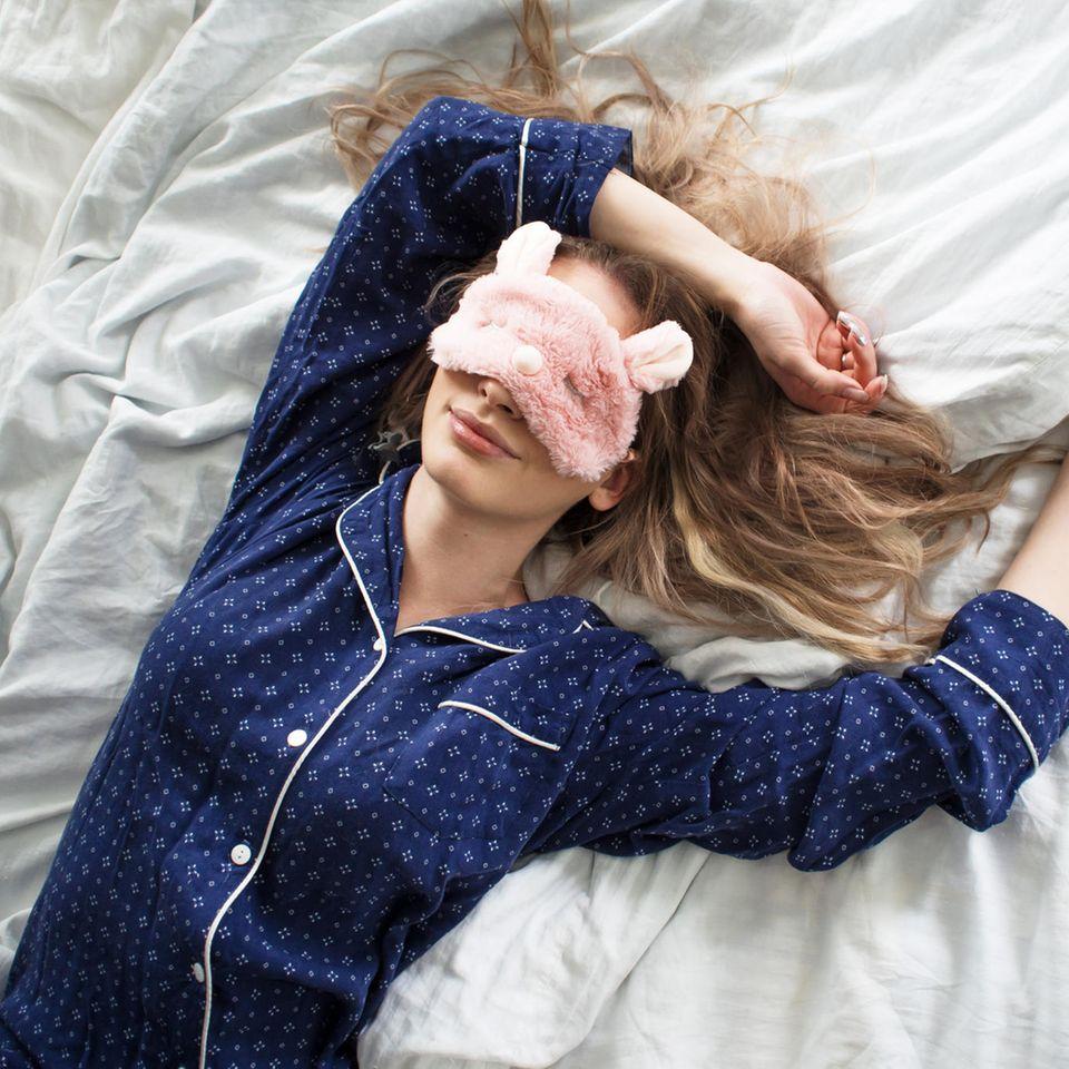 Schnell einschlafen: Frau mit Pyjama und Schlafbrille