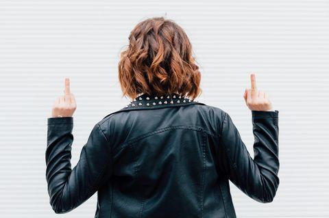 Stark sein ist nicht alles: Frau von hinten, während sie zwei Mittelfinger hoch hält