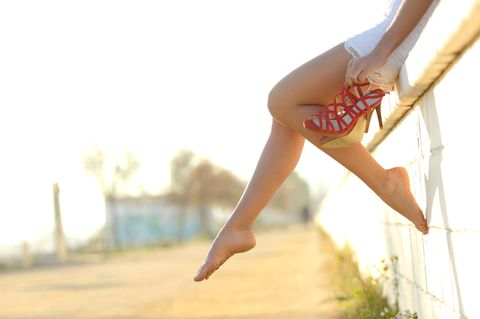 Schweißfrei durch den Sommer: Frau mit Sandalen auf einer Mauer