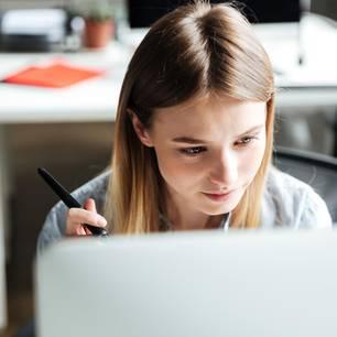 Konzentriert arbeiten: Junge Frau schaut auf Computer-Monitor