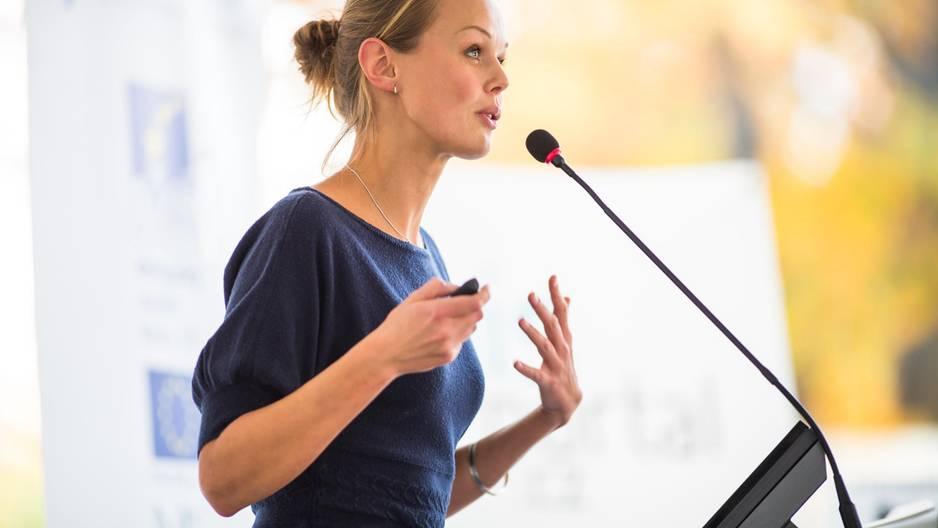 5 Tipps für eine selbstbewusste Körpersprache: Frau hält eine Rede