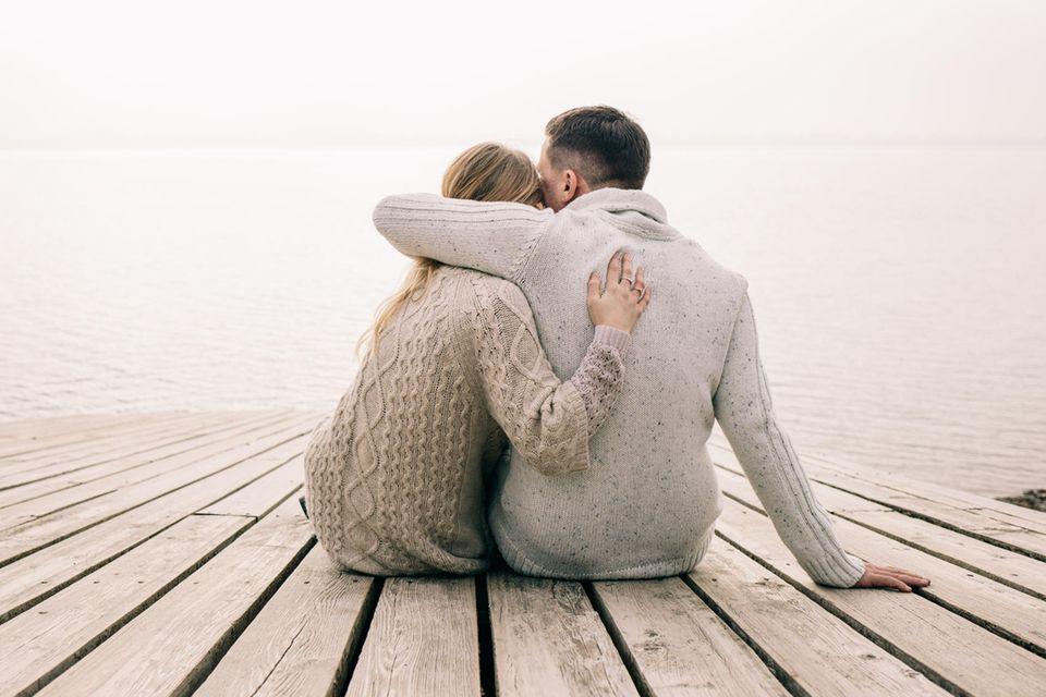Denkweisen, die die Beziehung gefährden: Paar sitzt auf dem Steg