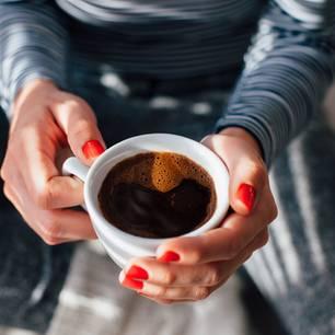 Kaffee-Typ: Frau hält schwarzen Kaffee