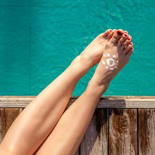 Sonnencreme auftragen: Frau mit Sonnencreme auf den Füßen