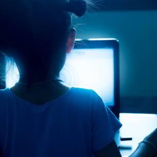Jugendschutz im Internet: Kind von hinten zu sehen, an einem Laptop sitzend