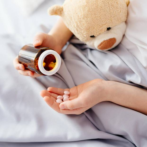 Vater gibt Kindern keine Medizin: Kinderhände mit Tabletten