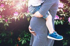 Mutter als Beruf: Eine Schwangere mit einem Kleinkind auf dem Arm