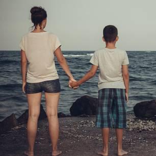 Angela Rose: Eine Frau und ihr Sohn schauen aufs Meer und halten sich an den Händen