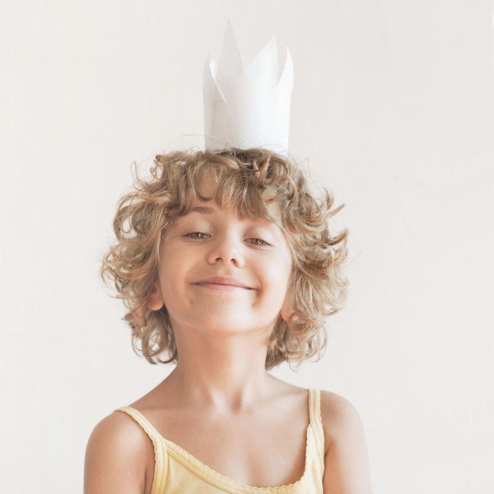 Kinder zu viel loben: Ein kleiner gelockter Junge mit Papierkrone auf dem Kopf