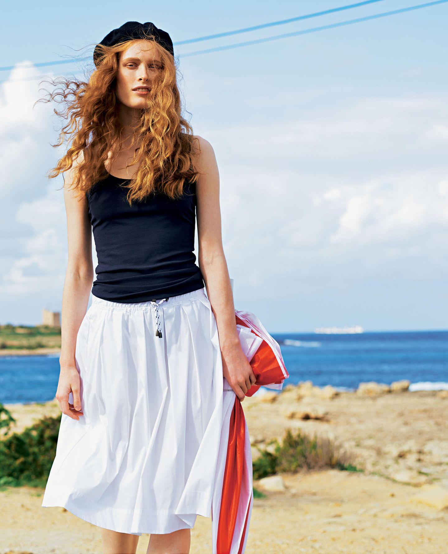 French Chic: Model mit Feinripp-Tanktop und weißem knielangem Faltenrock