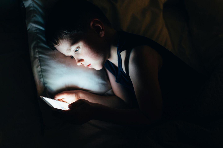 Momo-Challenge: Ein kleiner Junge im Bett mit Smartphone