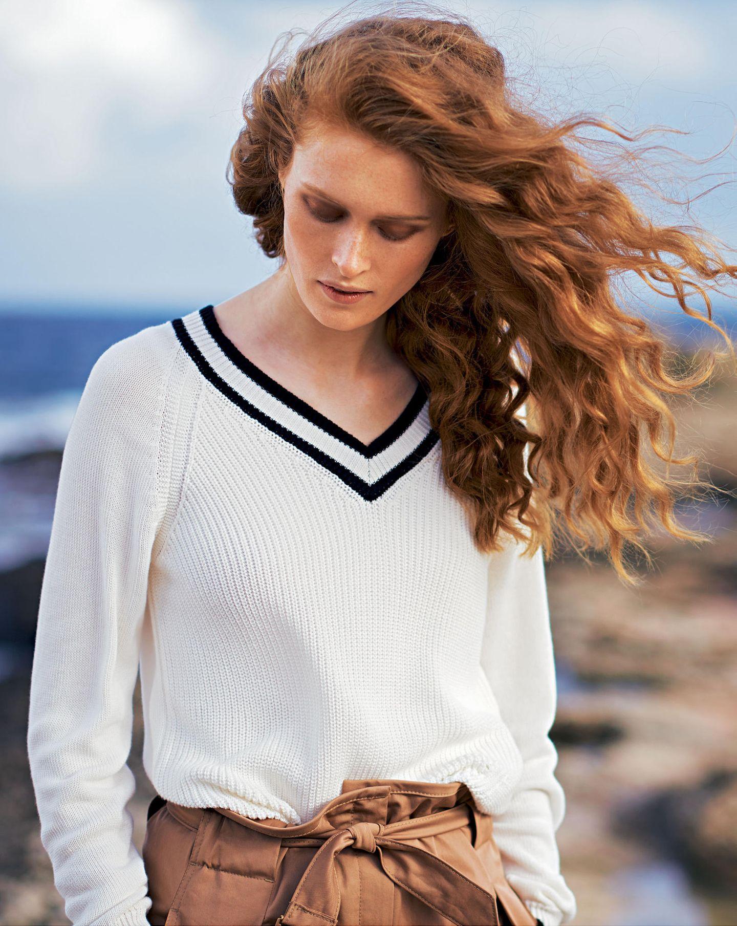 French Chic: Model mit weißem Tennispullover und Baumwollhose mit hohem Bund