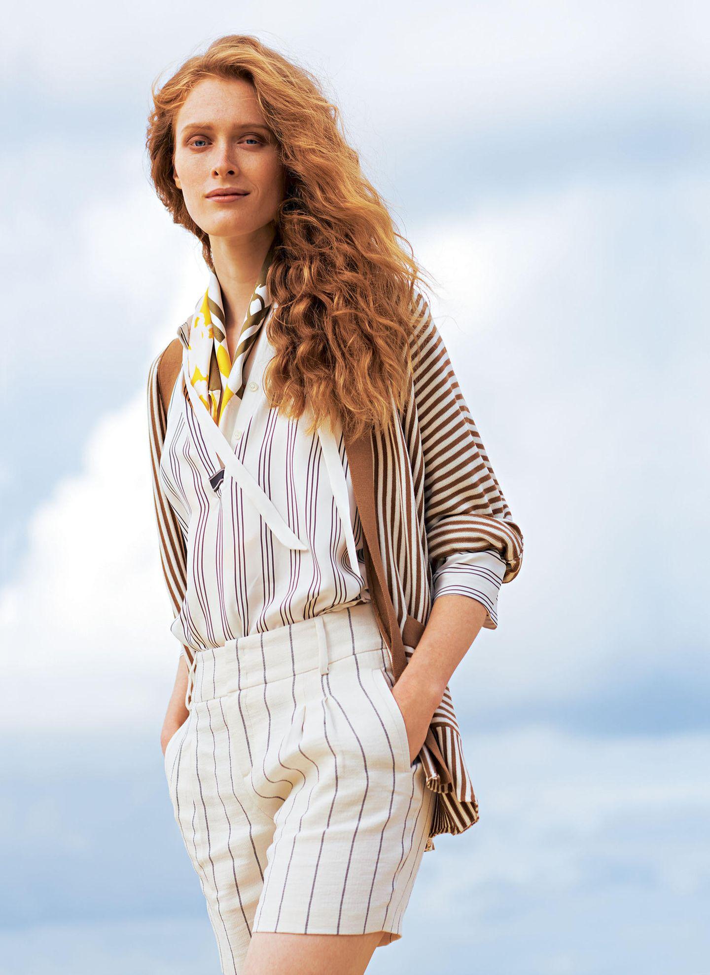 French Chic: Model mit Bluse aus Seide und Baumwoll-Strickjacke, dazu eine Shorts aus Leinen
