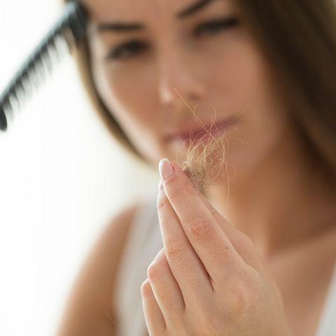 Haarausfall-Ursachen: Frau zieht Haare aus der Bürste
