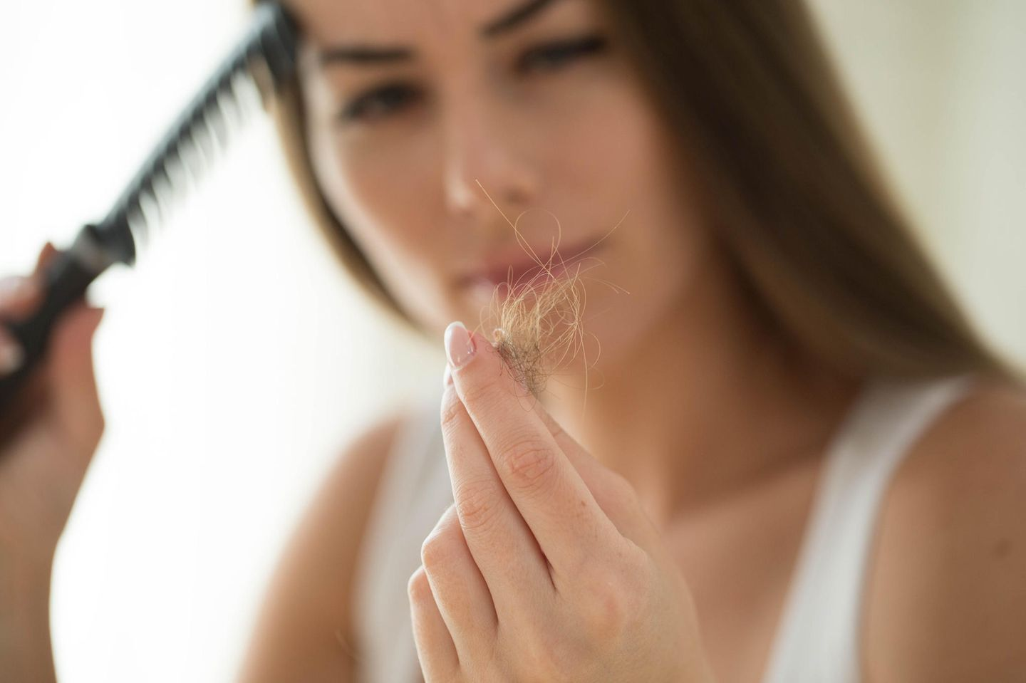 Causes of hair loss: woman pulls hair out of the brush