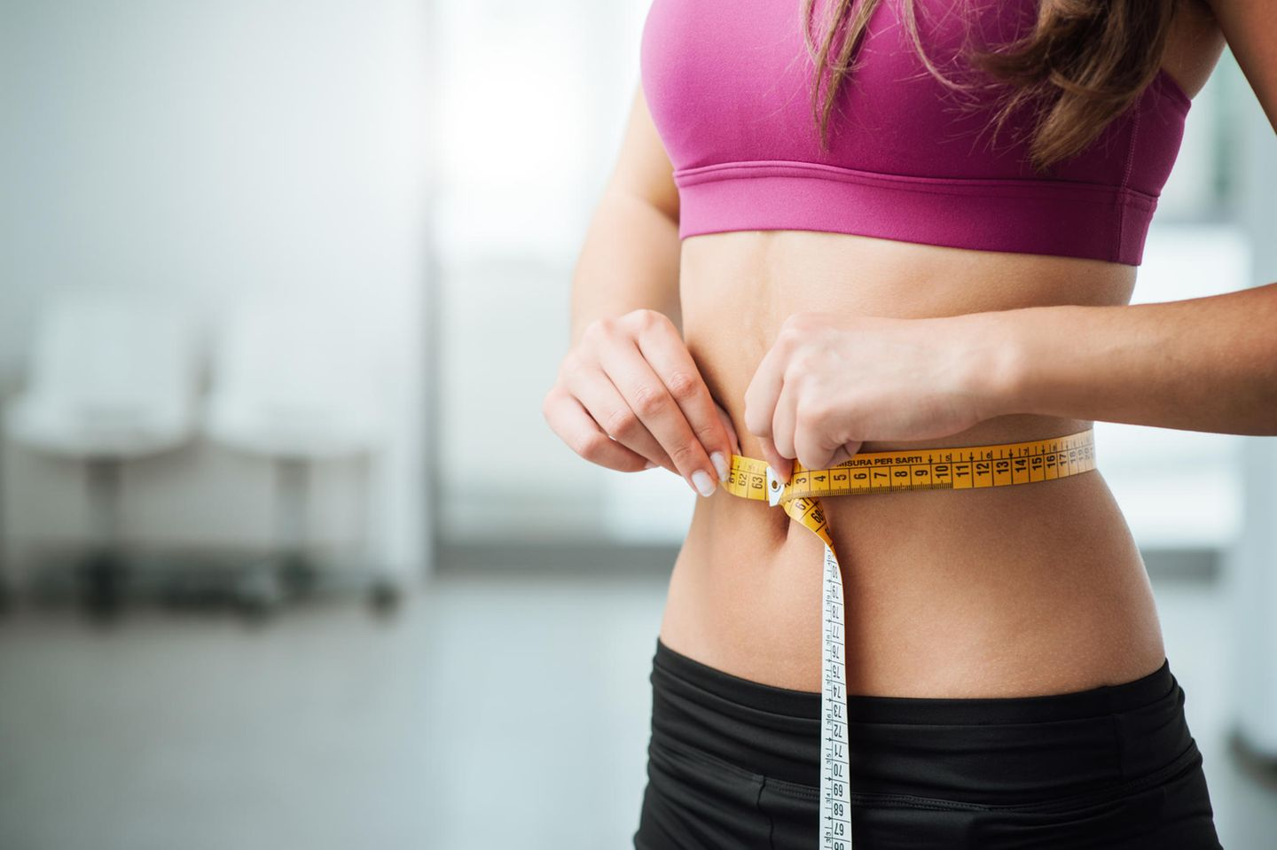Lose weight on the stomach: woman measures her waist with a tape measure