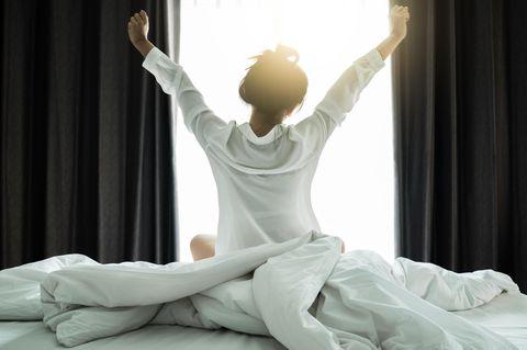 Diese Schlafregel gilt für alle Menschen: Eine Frau streckt sich im Bett