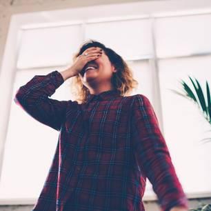 Dinge, für die sich niemand schämen muss: Eine junge Frau hält sich lachend die Augen zu