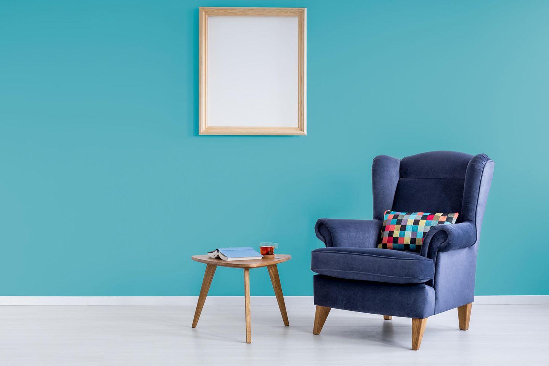Minimalistisch wohnen: Sessel und Tisch vor fast leerer Wand