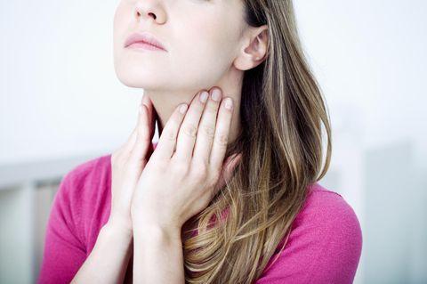 Eitrige Mandeln: Frau fasst sich an den Hals