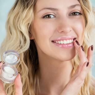 Jelly-Kosmetik: Frau streicht sich Creme auf die Lippen