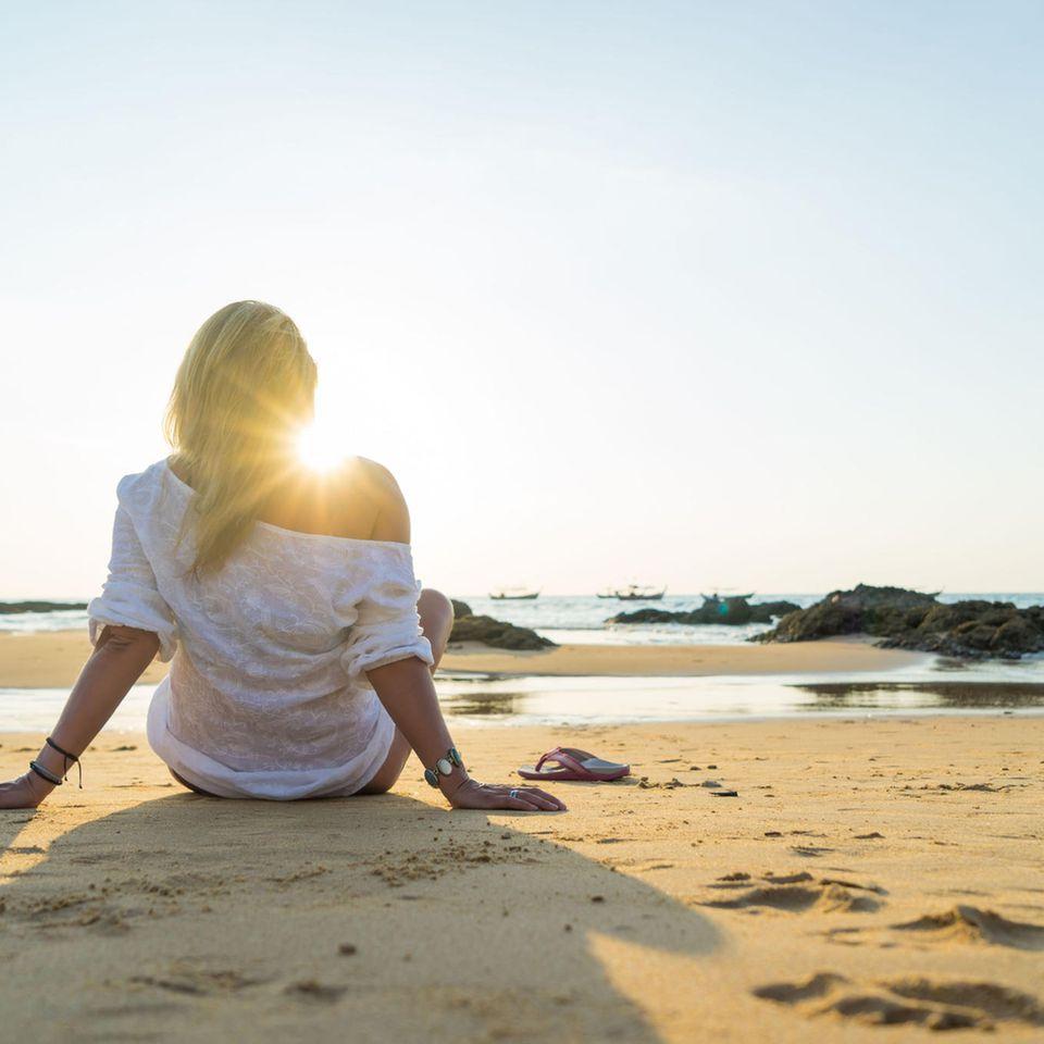 Krisen überstehen: Frau sitzt am Strand und ist von hinten zu sehen