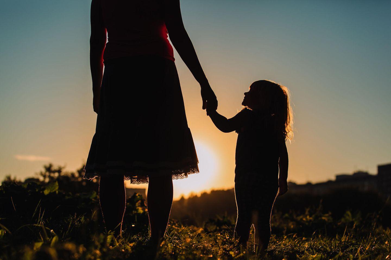Mutter mit Asperger-Syndrom: Mutter und Kind halten vor einem Sonnenuntergang Händchen