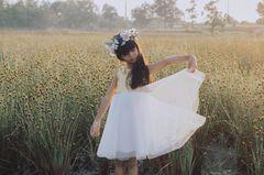 Elegante Vornamen: Ein Mädchen in weißem Kleid auf einer Wiese