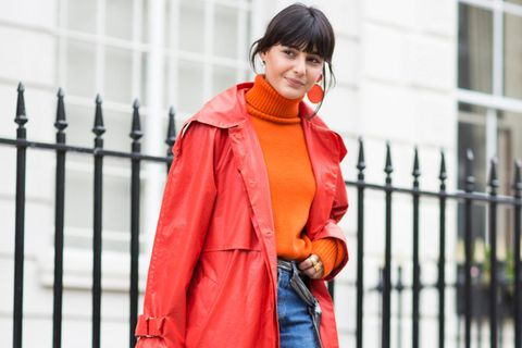 Frau mit rotem Mantel, Pullover in Orange und Schuhen in Lila