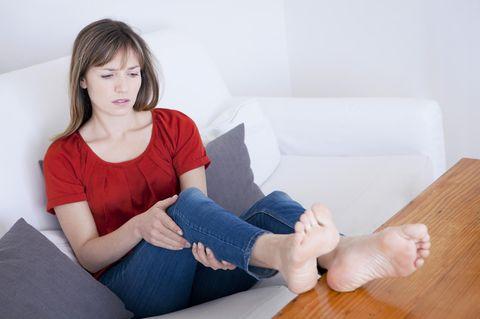 Schmerzen in den Beinen: Frau umfasst ihre Beine