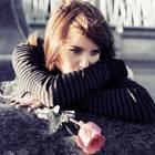 Herz gebrochen: Eine traurige junge Frau mit Rose in der Hand