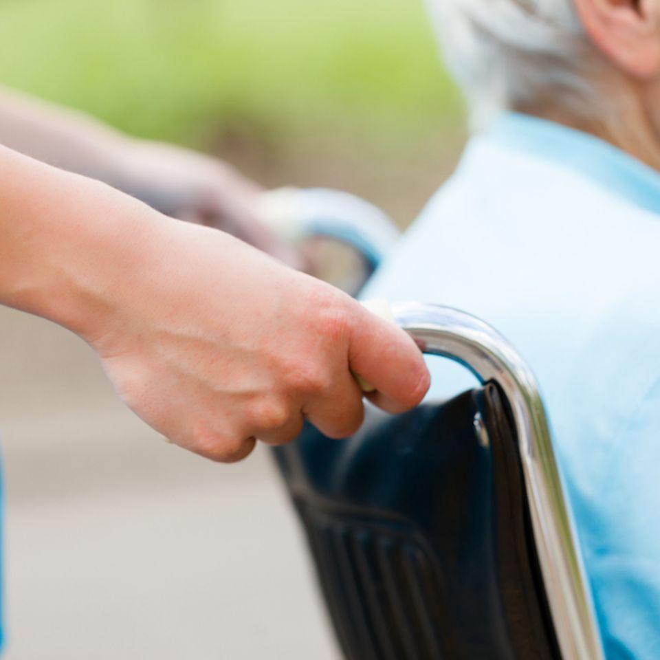 Eltern pflegen: ältere Person in Rollstuhl wird geschoben