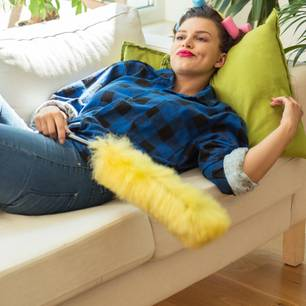 Aufschieberitis: Frau liegt mit Staubwedel auf der Couch