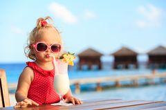 Cluburlaub mit Kindern: Kleines Mädchen schlürft Cocktail am Strand
