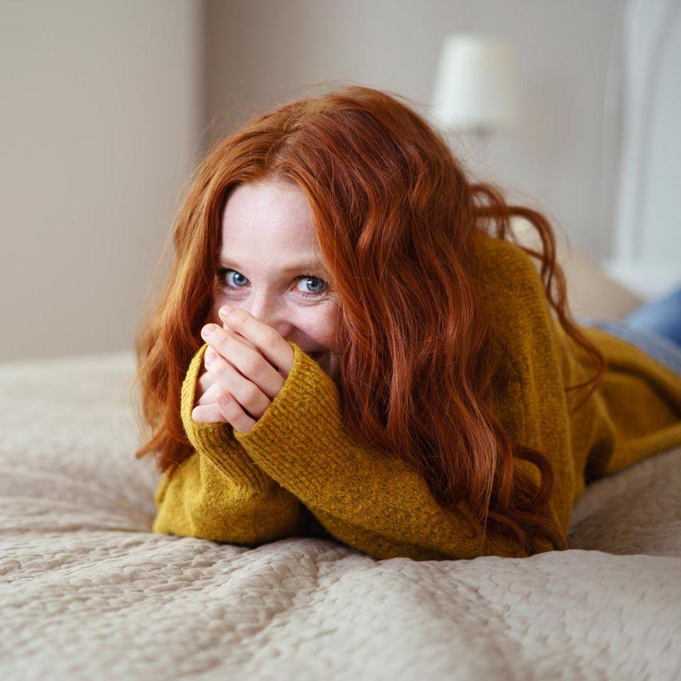 Introvertiere Menschen: Schüchterne Frau auf dem Bett