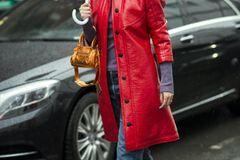 Frau mit Lackmantel und Regenschirm