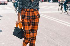 Streetstyle mit Hose in orangefarbenem Karomuster und gepunktetetr Bluse