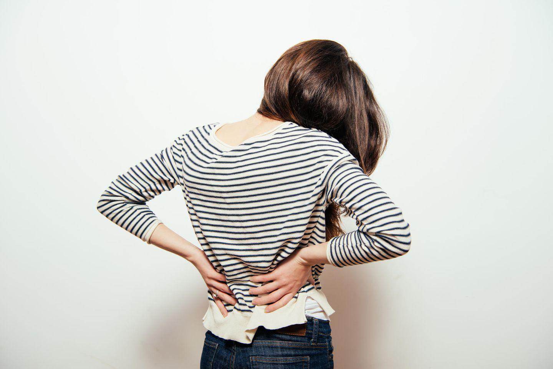 Rückenschmerzen-Ursachen: Frau hält sich den Rücken