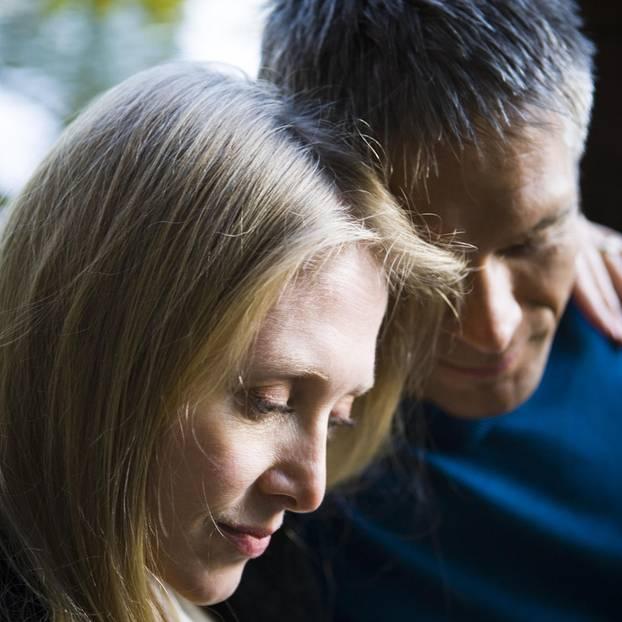 Partner depressiv: ein Paar, das nachdenkend auf den Boden schaut