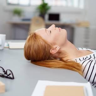 Montagsblues: Frau erschöpft am Schreibtisch