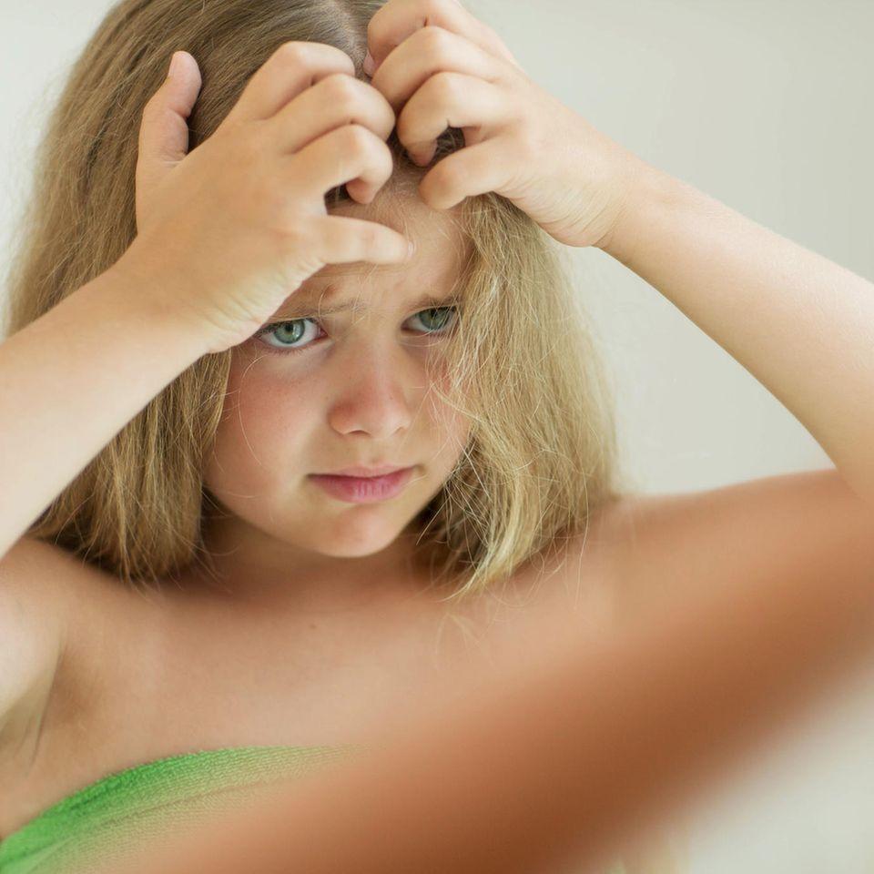Kopfläuse: Mädchen kratzt seinen Kopf