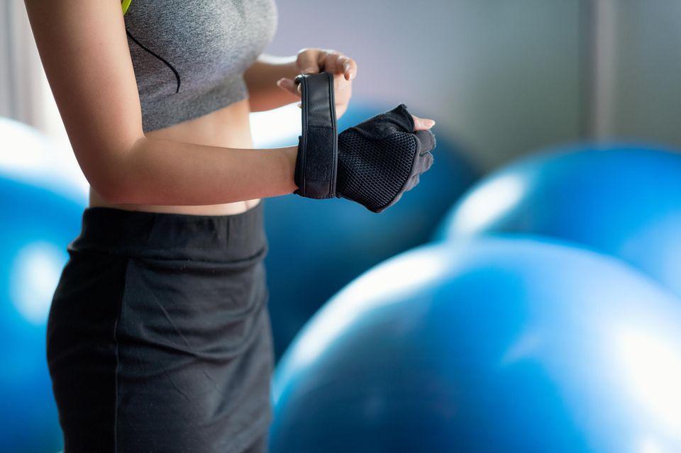 Dieser Trendsport macht dich schlank und fit: Frau zieht Trainingshandschuhe an