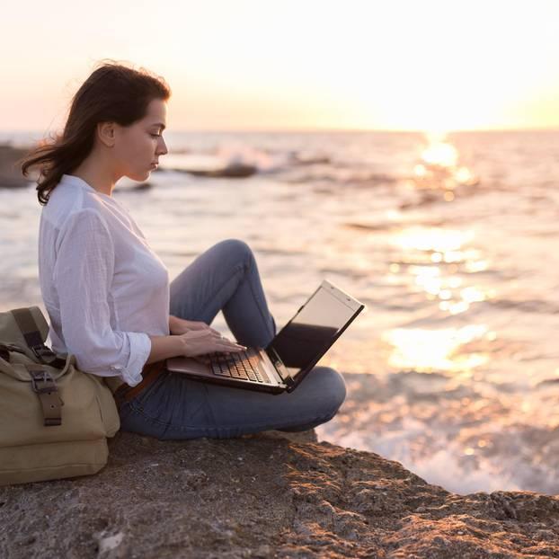 Jobpause: Frau sitzt mit Laptop am Meer