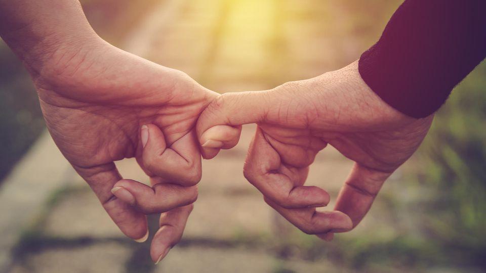 7 eindeutige Zeichen der Liebe: Mann und Frau halten einander an den kleinen Fingern