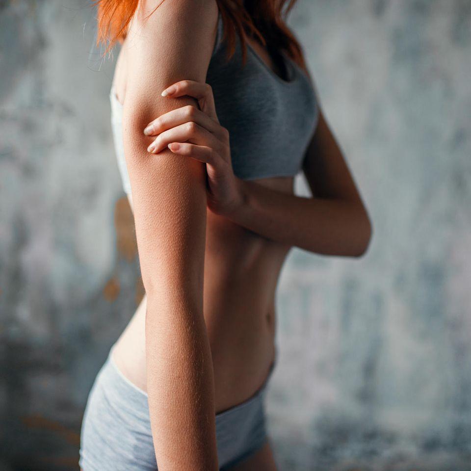 Tochter Magersucht: Dünnes Mädchen fasst sich an den Arm